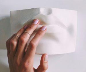 Fingers touching a sculpture of lips