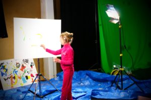 A woman works at a canvas with a light and green screen
