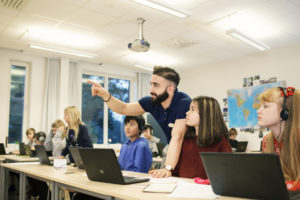 A man stands behind a laptop and desk with his hand raised for attention in a classroom in Solna