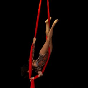 Woman suspended upside down beteen two ropes of red silk